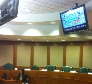 The video is displayed on a hearing room monitor